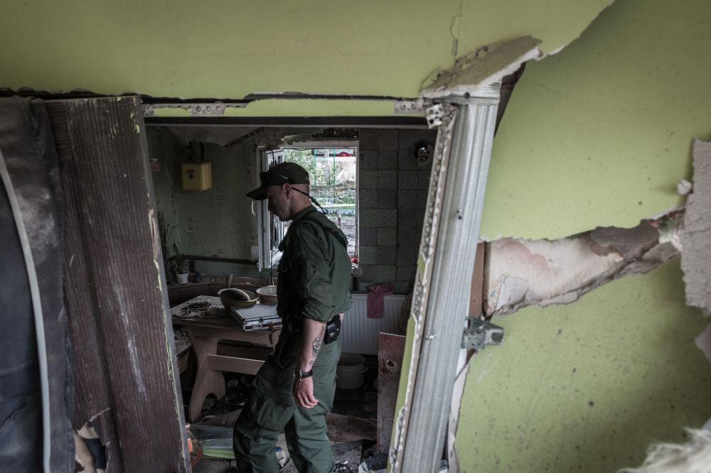 Membro das milícias populares da República Popular de Donetsk visita uma casa destruída pelos militares ucranianos em Gorlovka.