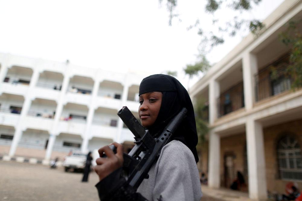 Menina deslocada da zona de combates na cidade de Hodeida, situada no mar Vermelho, posa com uma arma de brinquedo na cidade de Sanaa, Iêmen