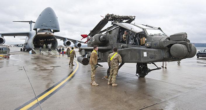 Helicóptero de ataque AH-64 Apache e um avião de transporte Galaxy C-5 estacionados na base aérea estadunidense de Ramstein, Alemanha