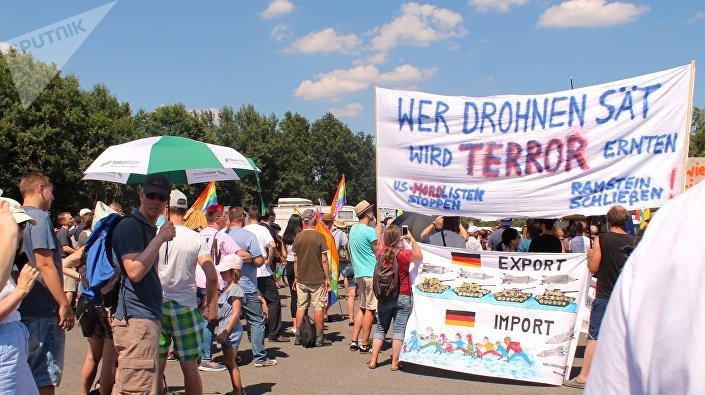Manifestantes com cartazes criticando guerra de drones e consequências de operações militares ocidentais no exterior