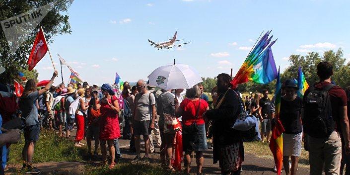 Avião militar americano sobrevoando manifestantes durante protesto.