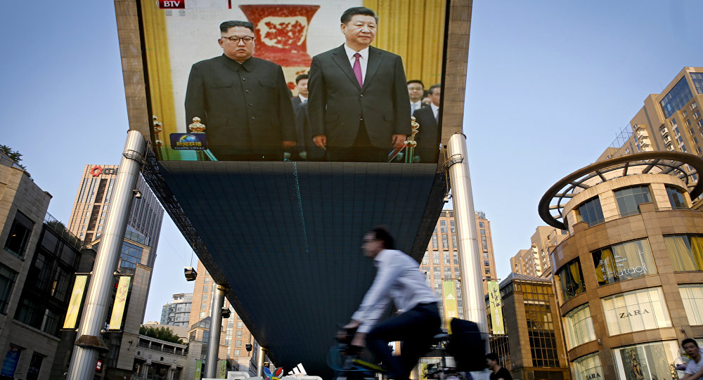 As pessoas andam de bicicleta passando por um teção transmitindo a reunião do líder norte-coreano Kim Jong Un e do presidente chinês Xi Jinping durante uma cerimônia de boas-vindas no Grande Salão do Povo em Pequim, terça-feira, 19 de junho de 2018.