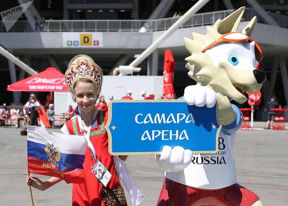 Menina em traje tradicional russo posa junto a Zabivaka (aquele que marca um gol, em russo) – a mascote oficial da Copa do Mundo FIFA de 2018, celebrada na Rússia