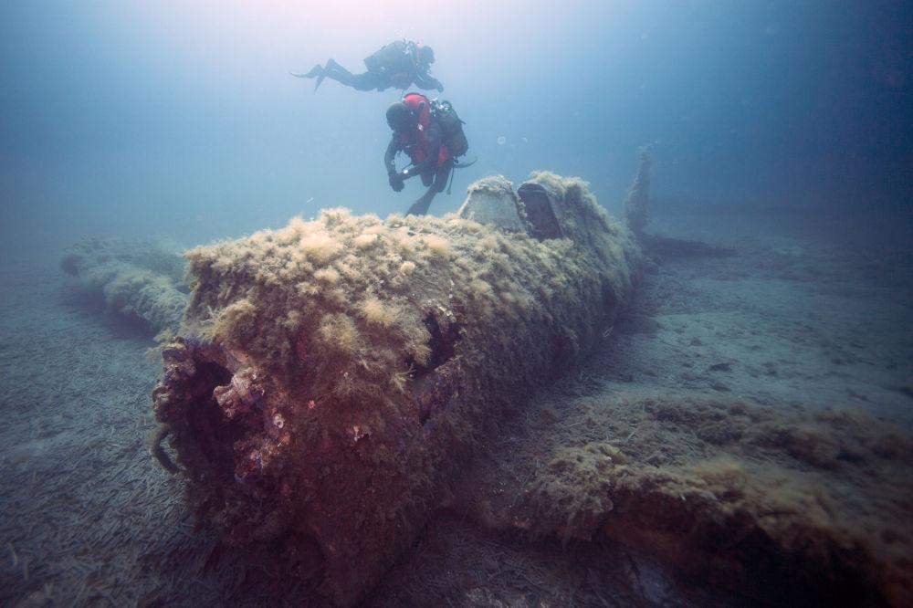 Mergulhadores militares franceses nadando sobre os destroços do avião norte-americano P-47 Thunderbolt afundado perto da ilha de Córsega na época da Segunda Guerra Mundial