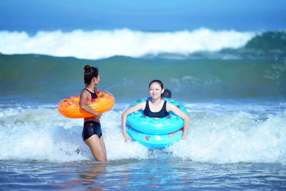 Moças na praia da cidade chinesa de Qingdao, província Shandong