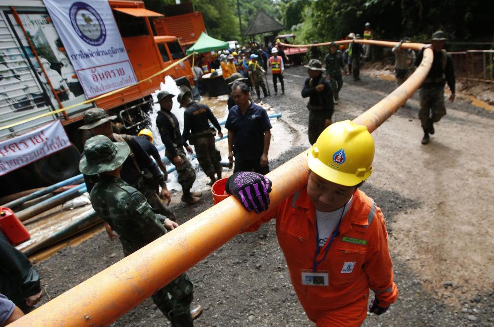 Homens segurando um tubo de adutora durante a operação de resgate das crianças em gruta na Tailândia