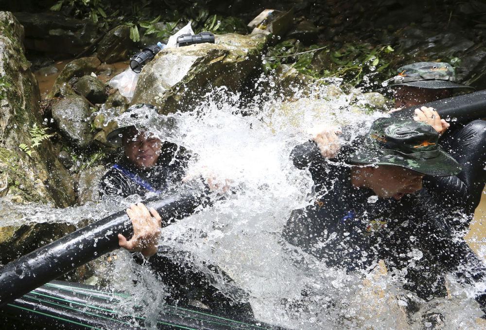 Salvadores tailandeses instalam tubos durante a operação de resgate dos meninos da caverna inundada