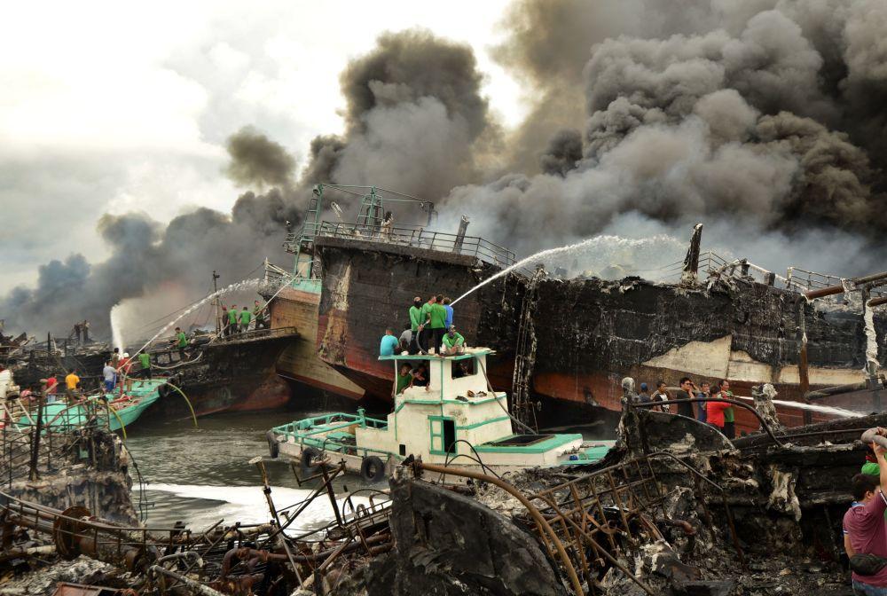 Bombeiros tentam eliminar fogo em barcos de pesca, na Indonésia