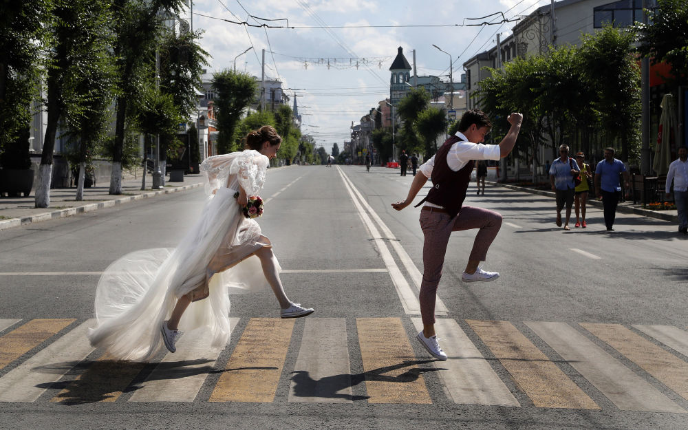 Recém-casados posam para foto ao atravessar a estrada durante a Copa 2018 em Samara, na Rússia
