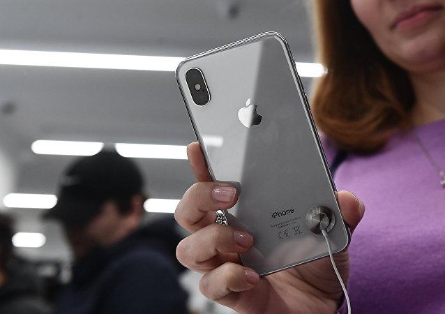 Compradora examina novo smartphone iPhone X em uma loja, em Moscou