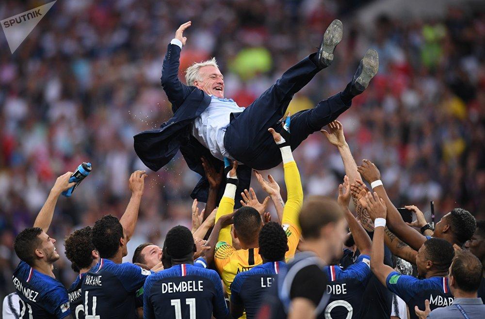 Os jogadores da seleção francesa jogam para cima o técnico da França, Didier Deschamps comemorando a vitória contra Croácia na final da Copa do Mundo.