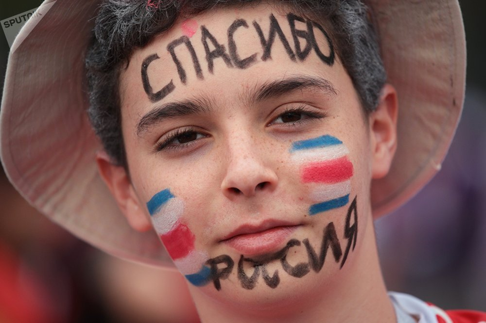 Jovem torcedor com as inscrições Obrigado, Rússia no rosto antes do jogo entre França e Croácia pelo final da Copa do Mundo