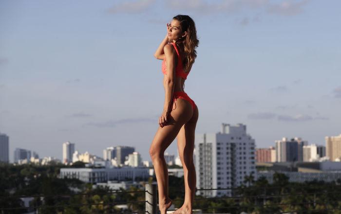 Modelo posa vestindo biquíni na Miami Swim Week com vista da cidade em segundo plano