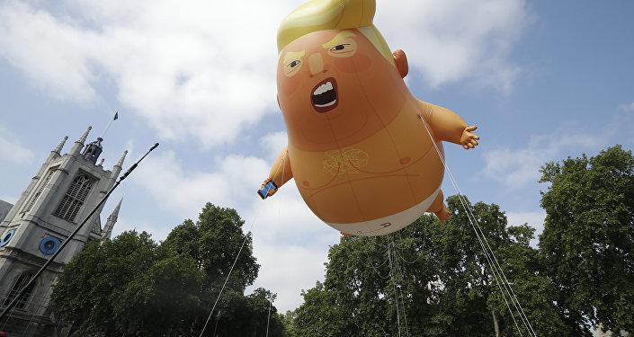 Um dirigível infantil de seis metros representando o presidente dos EUA, Donald Trump, é levado como protesto contra sua visita, ao Parliament Square, Londres.