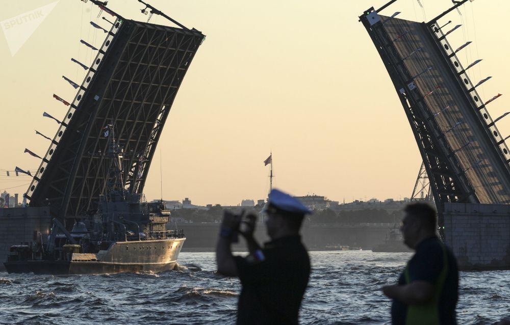 No dia do ensaio de desfile militar, um navio de guerra de minas navega debaixo de uma ponte que atravessa o rio Neva, São Petersburgo