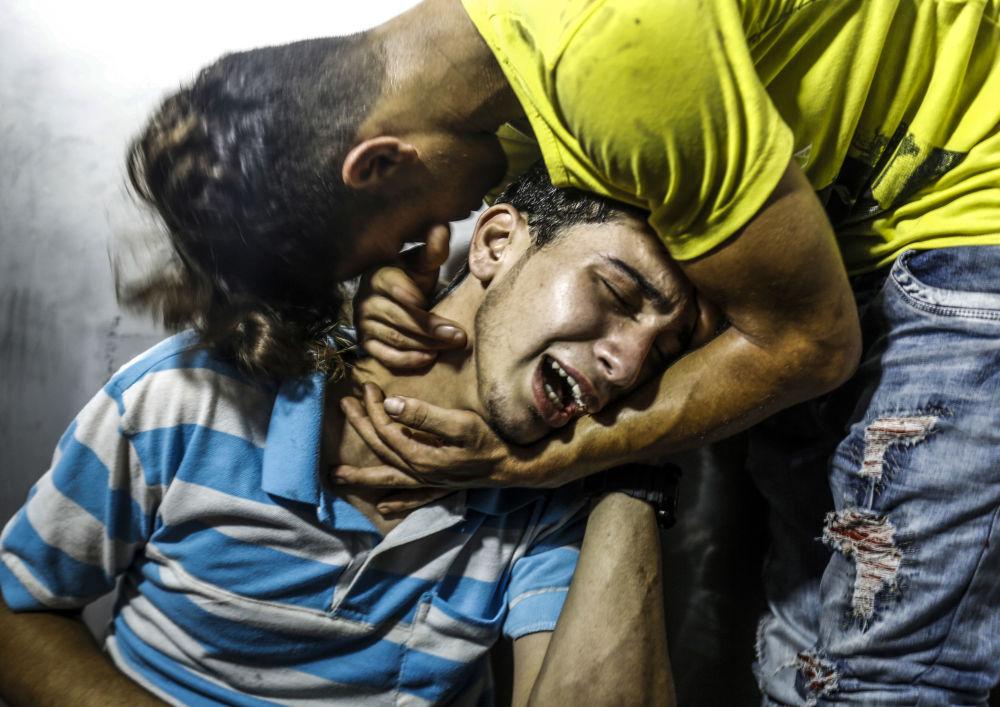 Palestinos chorando a morte de dois adolescentes mortos em um dos ataques aéreos de Israel à Faixa de Gaza.
