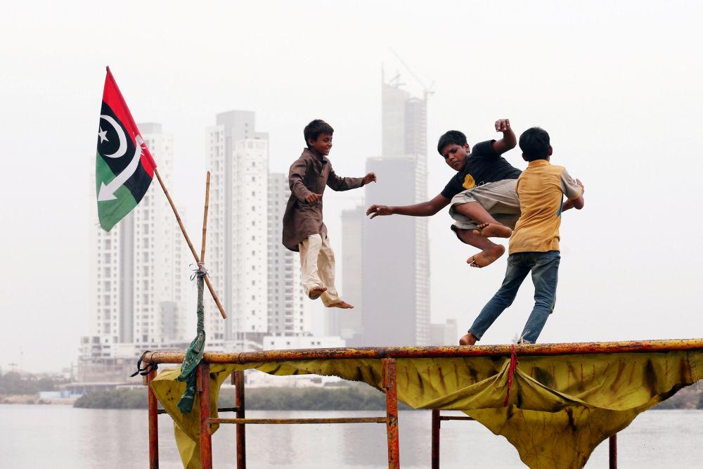 Crianças brincando em um trampolim em um bairro pobre de Karachi, Paquistão.