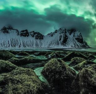 Mágica por Jingyi Zhang. Magnífica aurora boreal rompe nuvens iluminando os montes na península de Stokksnes, Islândia