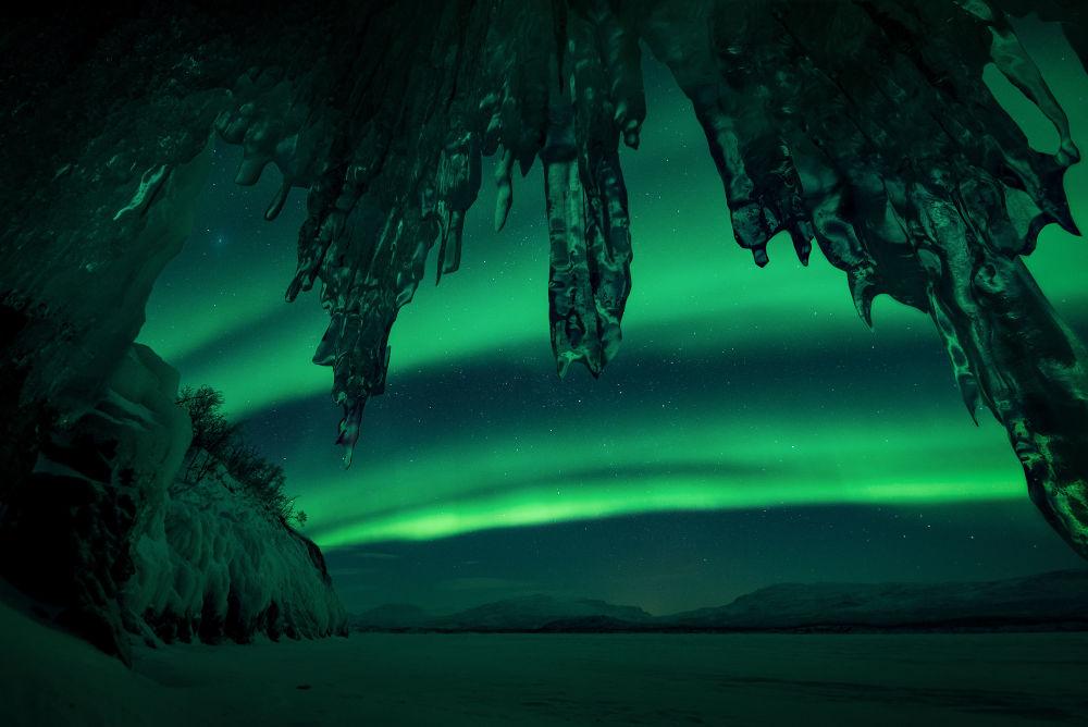 Castelo de gelo por Arild Heitmann. A imagem marcante em que a aurora polar lança luzes verdes sobre enormes estruturas de gelo, com temperaturas de 26 °C negativos, em Lapônia, Suécia