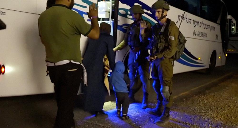 Capacetes Brancos entrando em um ônibus durante a evacuação da Síria assegurada por soldados israelenses, 22 de julho de 2018