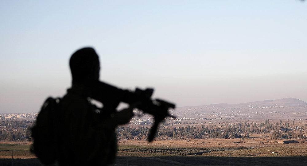 Um soldado israelense vigiando a linha de demarcação que separa o território sírio e israelense