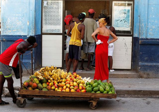 Homem puxando carrinho com frutas em frente de um mercado com a imagem de Raul Castro, Havana, Cuba.