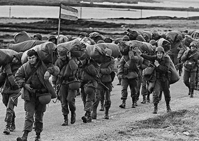 Soldados argentinos caminhando para ocupar a base capturada dos Royal Marines (fuzileiros reais em português) em Porto Argentino/Port Stanley poucos dias após a ditadura militar argentina ter tomado as ilhas Malvinas, iniciando uma guerra entre a Argentina e o Reino Unido, 13 de abril de 1982