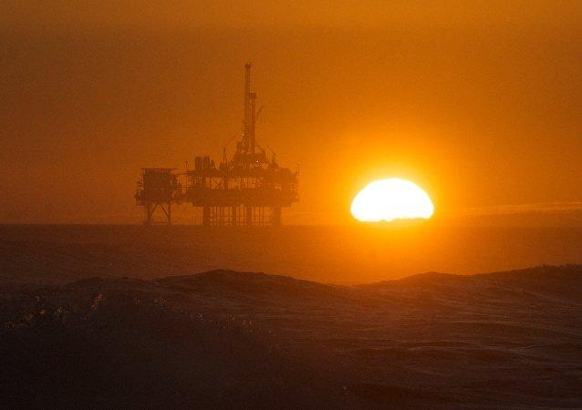 Pôr do sol sobre a plataforma de petróleo.