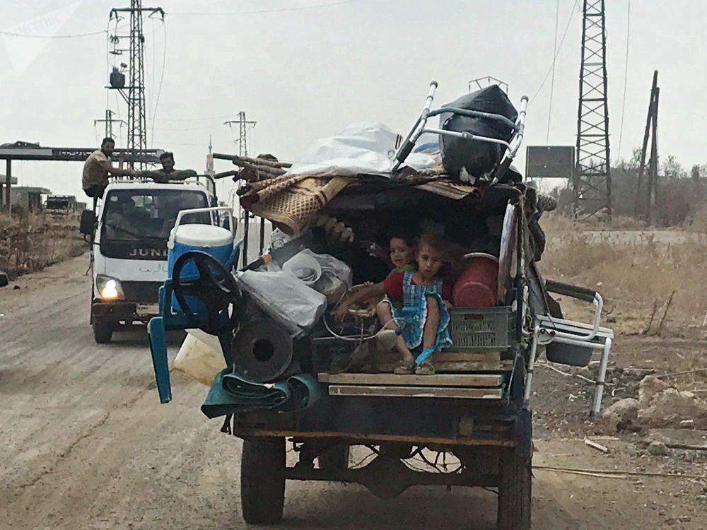Meninos na carroceria de um carro no sudoeste da província libertada de Daraa