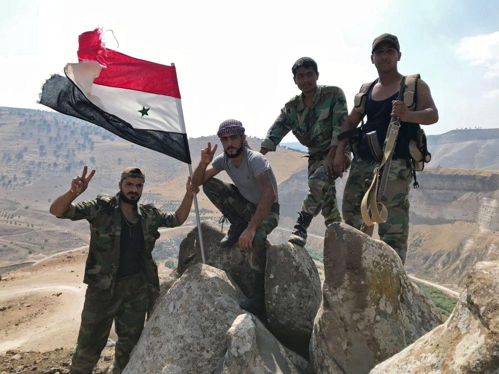 Militares sírios hasteiam bandeira governamental no sudoeste da província de Daraa, na fronteira com a Jordânia