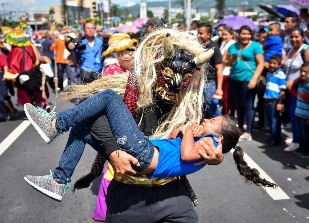 Pessoa com fantasia de uma criatura mitológica carregando uma menina durante uma parada em San Salvador