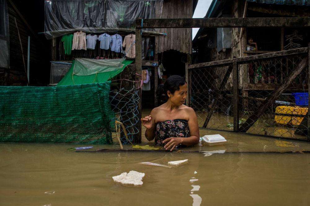 Mulher anda pela rua inundada na cidade de Bago, em Mianmar