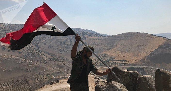 Militar sírio hasteia bandeira da Síria no sudoeste da província de Daraa, na fronteira com a Jordânia