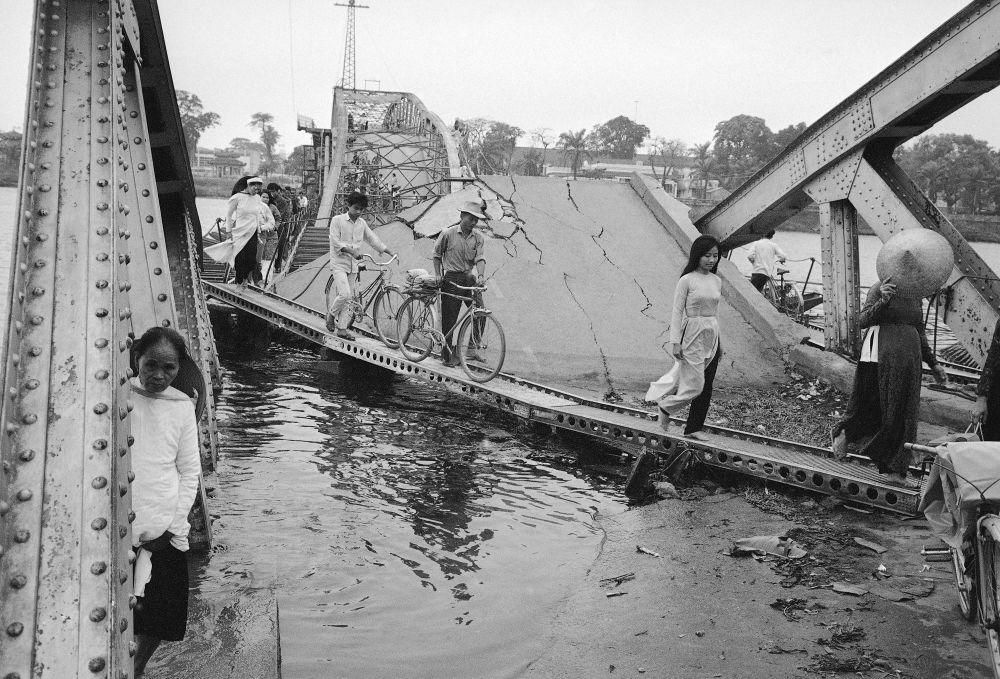 Residentes atravessam uma ponte destruída na cidade de Hue, no Vietnã