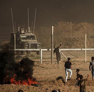 Manifestantes palestinos atiram pedras contra as forças israelenses durante uma manifestação na fronteira entre Israel e a Faixa de Gaza, a leste da cidade de Gaza em 27 de julho de 2018