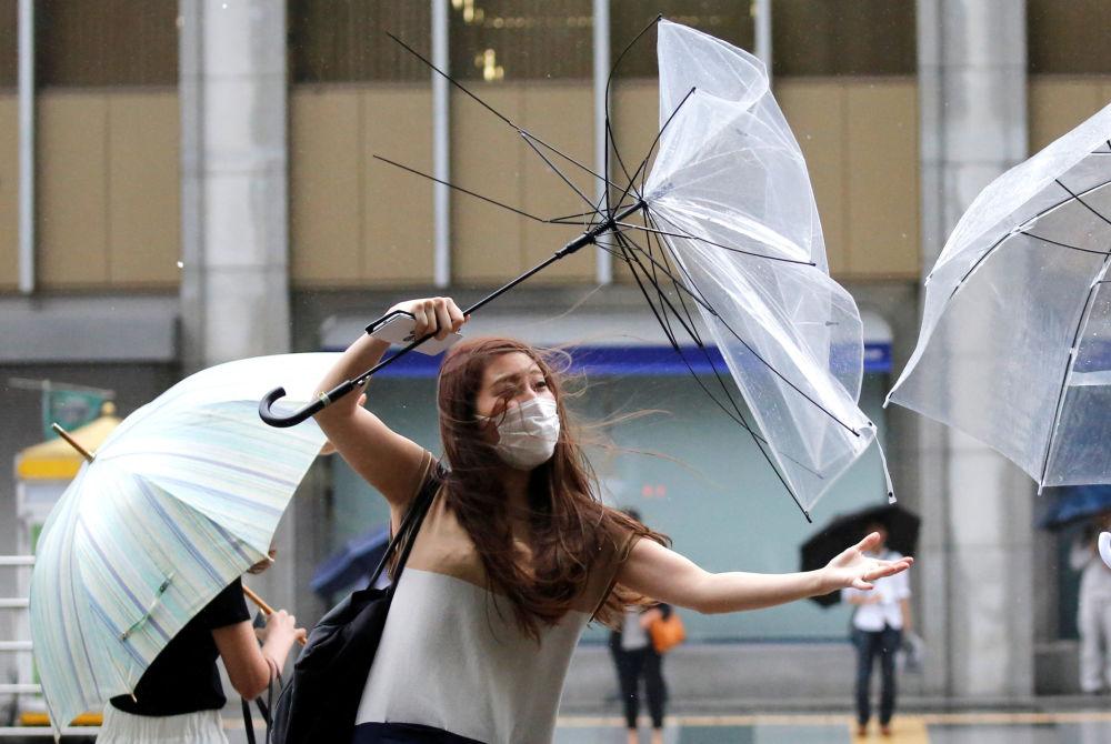 Moça tenta endireitar um guarda-chuva, em Tóquio
