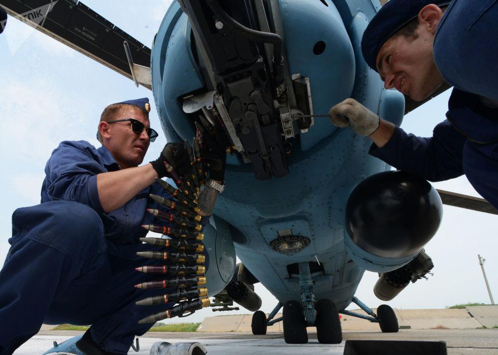 Técnicos aeronáuticos examinando um helicóptero Mi-35 durante manobras no aeródromo de Chernigovka na região de Primorie