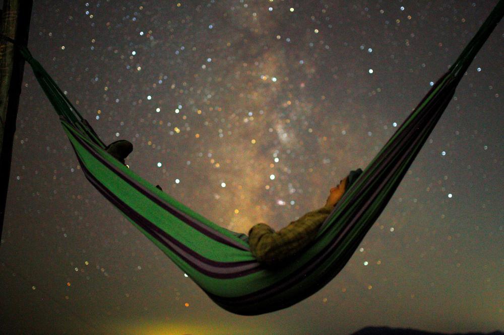 Menina relaxa e observa as estrelas cadentes na Macedônia, em 13 de agosto
