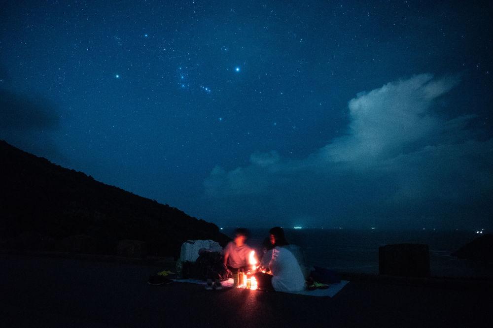 Pessoas observam o céu estrelado durante um piquenique na beira-mar em Hong Kong