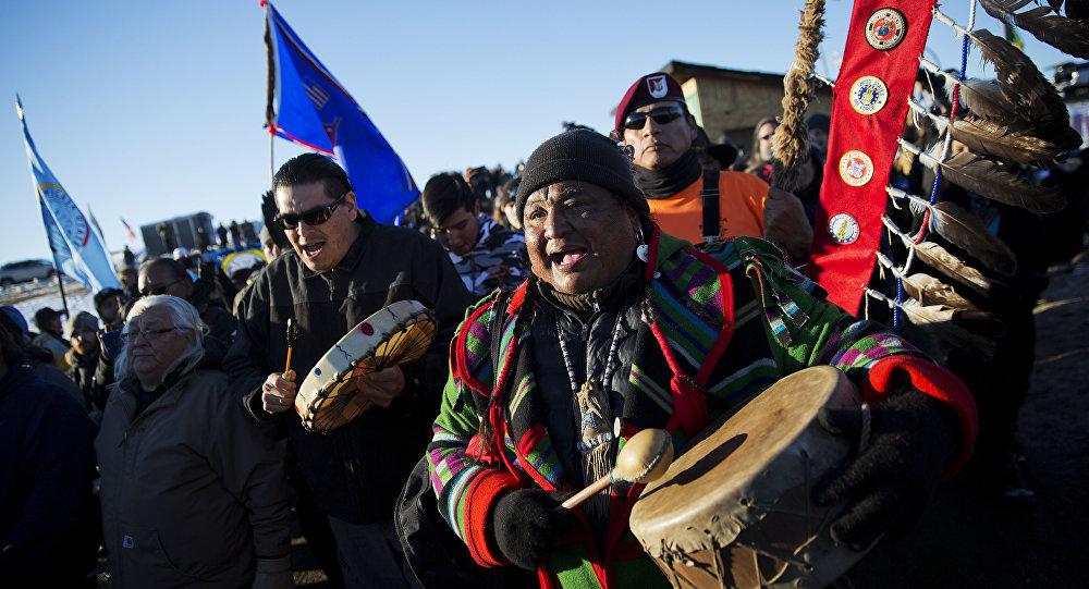 Dan Nanamkin, da tribo nativa norte-americana em Nespelem, Wash, comemoram com instrumentos uma procissão pelo acampamento Oceti Sakowin nos EUA, em 4 de dezembro de 2016