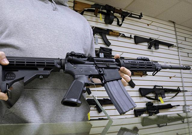 John-Jackson, um dos donos da Capitol City Arms Supply, mostra um rifle de assalto AR-15 que está a venda.