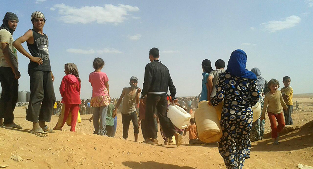 Refugiados sírios se reúnem em busca de água no campo de refugiados de Rukban, na fronteira nordeste da Jordânia com a Síria (Arquivo)