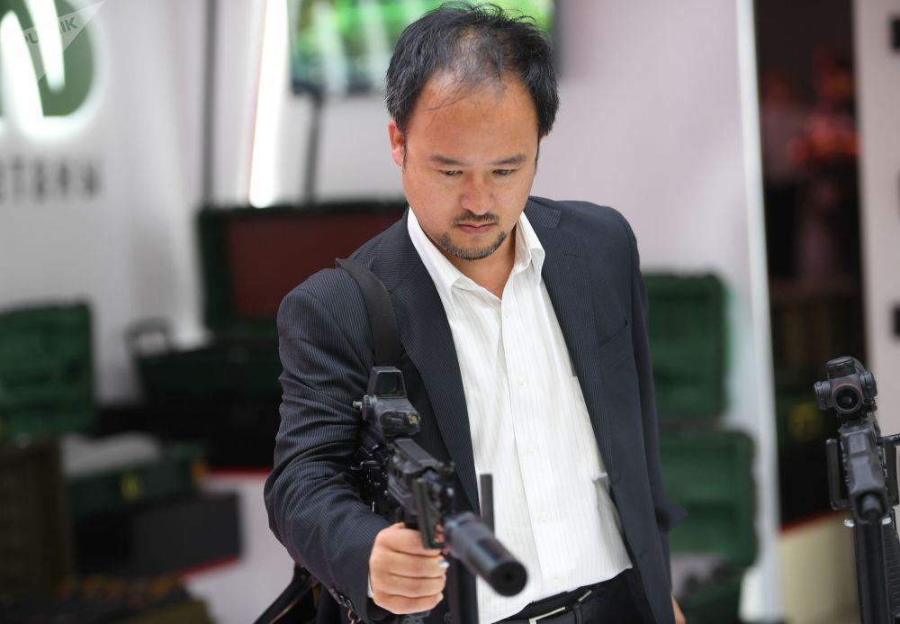 Um visitante segurando o fuzil de assalto Ak-15 apresentado pelo consórcio russo Kalashnikov no Fórum Internacional Técnico-Militar EXÉRCITO 2018