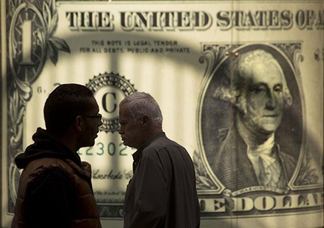 Egípcios passam por um pôster mostrando o dólar americano fora de uma casa de câmbio no Cairo, Egito, 3 de novembro de 2016