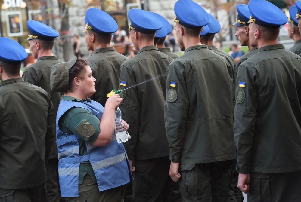 Enfermeira refresca soldados com água durante um ensaio da parada militar no Dia da Independência da Ucrânia