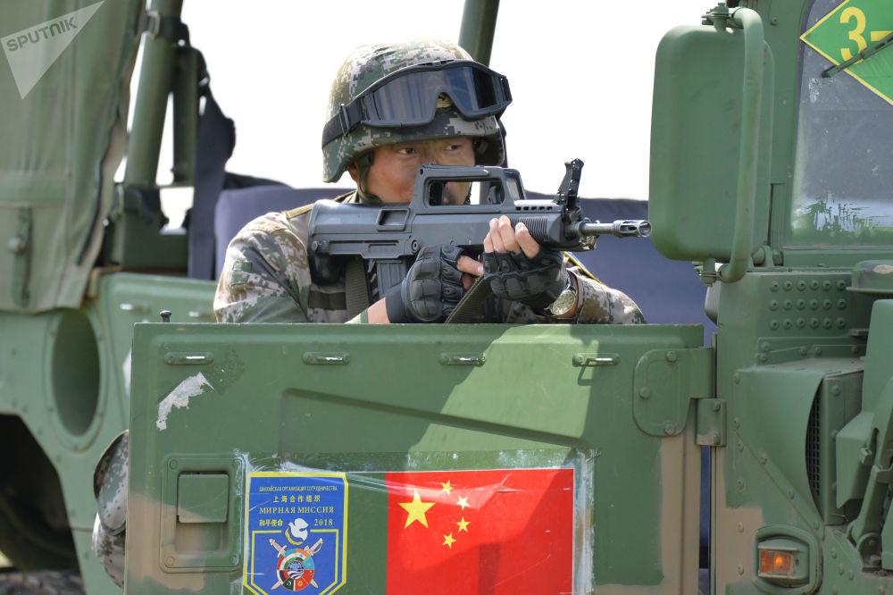 Atirador especial chinês prepara-se para atingir um alvo inimigo virtual no decurso dos treinamentos militares da OCX