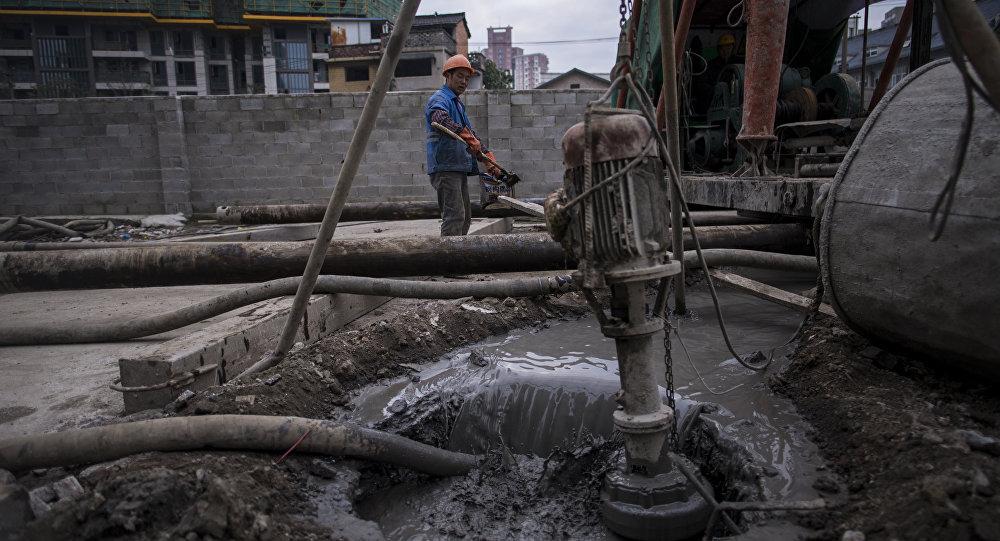 Homem coloca cimento dentro do carrinho de mão em uma área de construção civil, Xangai, China, 29 de novembro de 2016 (foto de arquivo)