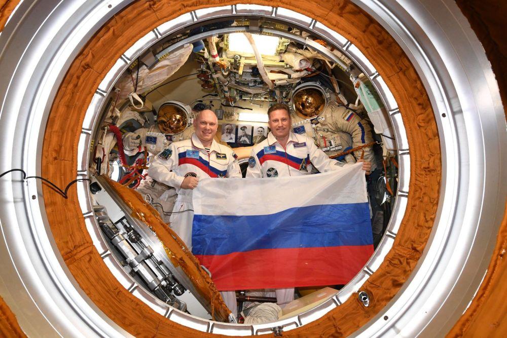 Astronautas russos Oleg Artemiev e Sergei Prokofiev segurando a bandeira da Rússia a bordo da Estação Espacial Internacional no Dia da Bandeira russa