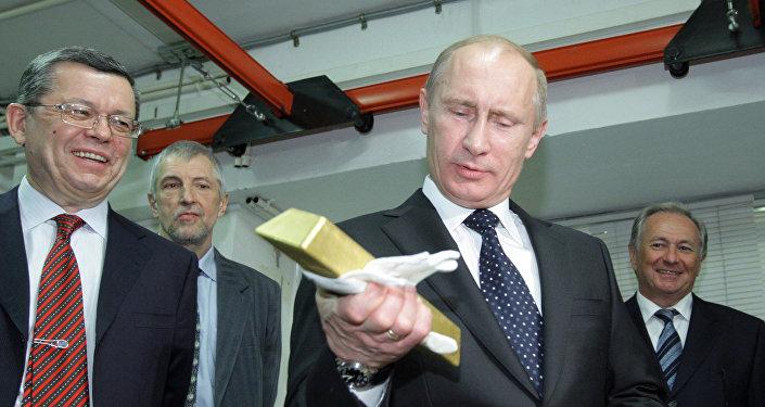 Presidente russo Vladimir Putin segurando uma barra de ouro enquanto visitava o Depositário Central do Banco da Rússia (foto de arquivo)