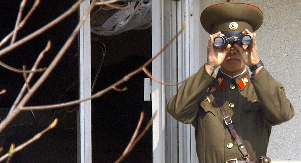 Soldado norte-coreano olha para o lado sul através de binóculos na vila fronteiriça de Panmunjom, na zona desmilitarizada que divide a Coreia do Norte e a Coreia do Sul, em 13 de abril de 2005
